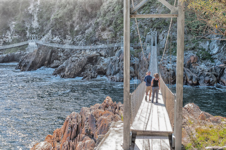 nature conservancy: STORMS RIVER MOUTH, SOUTH AFRICA - FEBRUARY 28, 2016:  Unidentified tourists on one of the three suspension bridges at the mouth of the Storms River