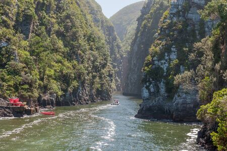 nature conservancy: STORMS RIVER MOUTH, SOUTH AFRICA - FEBRUARY 29, 2016:  Unidentified tourists on an inflatable speedboat entering the Storms River gorge