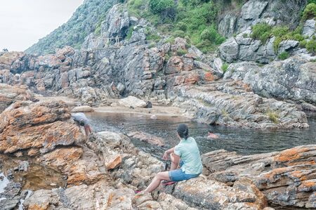 end of the trail: STORMS RIVER MOUTH, SOUTH AFRICA - MARCH 1, 2016:  Unidentified tourists at the pool below the waterfall at the end of the Waterfall Trail on an overcast day. The trail follows part of the renowned Otter trail Editorial