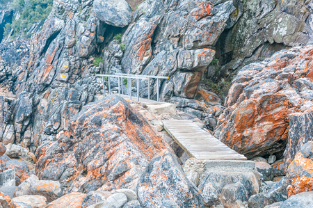 return trip: Two bridges on the Waterfall Trail at Storms River Mouth on an overcast day, a difficult 6.4 km return trip through rugged terrain along the coastline Stock Photo