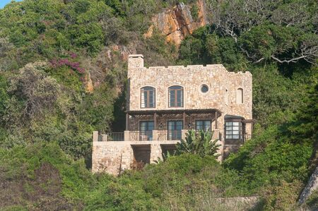 KNYSNA, SOUTH AFRICA - MARCH 5, 2016: A house on the slopes of a hill in Noetsie. Noetsie is a popular tourist attraction due to the houses that were built to look like castles.