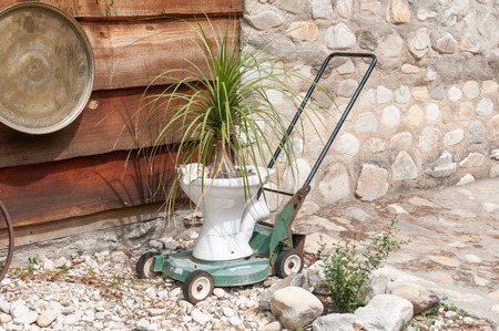 innovative: Innovative recycling of an old lawnmower and toilet bowl into a decorative display Stock Photo