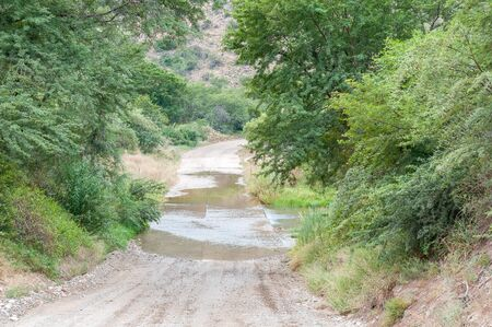 crossings: The road through the Baviaanskloof (baboon valley) crosses the Baviaans River on a concrete causeway, one of many such crossings on the road Stock Photo