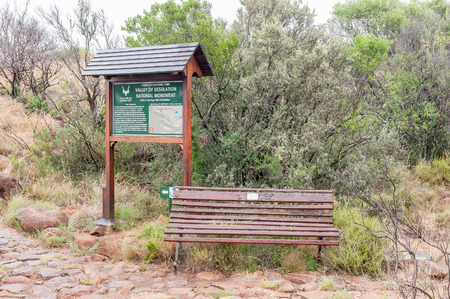 desolation: GRAAFF REINET, SOUTH AFRICA - MARCH 7, 2016: An information board and bench at the start of the Crag Lizard trail near the Valley of Desolation viewpoint