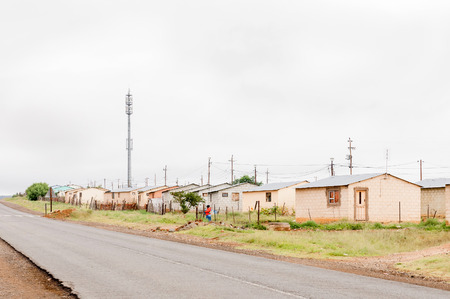 low income housing: MIDDELBURG, SOUTH AFRICA - MARCH 8, 2016: An unidentified woman iin front of low income housing in Kwanonzame, a township in Middelburg in the Eastern Cape Karoo Region Editorial
