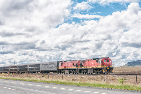 COLESBERG, SOUTH AFRICA - MARCH 8, 2016: Two diesel-electric locomotives pulling a train through typical Karoo landscape between Noupoort and Colesberg in the Northern Cape Province Reklamní fotografie - 57384482