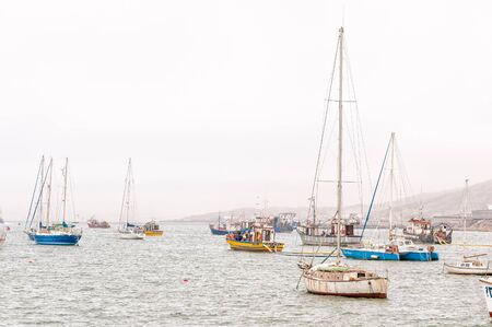 luderitz: LUDERITZ, NAMIBIA - JUNE 14, 2011: Sail yachts and fishing boats in misty conditions at the harbor in Luderitz in Namibia Editorial