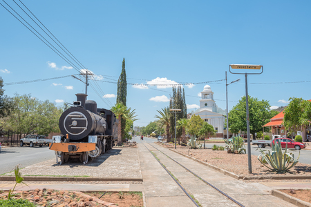 FAURESMITH, SOUTH AFRICA - DECEMBER 31, 2016: A steam locomotive and the town hall in Fauresmith, one of only three towns on earth where the railway line runs down the centre of the main road Editorial