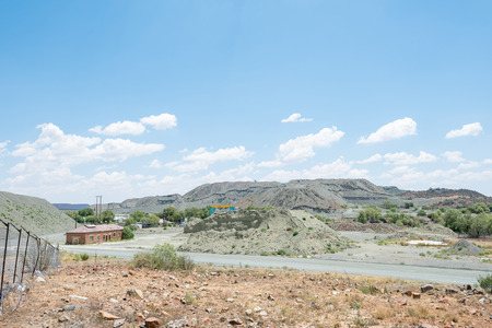dumps: JAGERSFONTEIN, SOUTH AFRICA - DECEMBER 31, 2016: Mine dumps and infrastructure in Jagersfontein. The town claims the title of oldest mining town in South Africa and biggest hand dug hole in the world Editorial