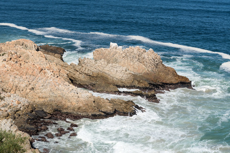 A rocky outcrop, resembling a dragon, in the sea next to Clarence Drive between Gordons Bay and Rooi-Els Stock Photo