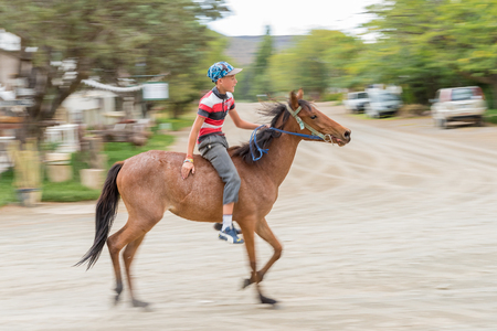 bethesda: NIEU BETHESDA, SOUTH AFRICA - MARCH 21, 2017: An unidentified rider on a horse galloping through the streets of Nieu-Bethesda, an historic village in the Eastern Cape Province