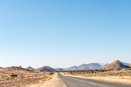 De B1-weg tussen Grunau en Keetmanshoop in de Karas-regio van Namibië. Het Great Karas-gebergte bevindt zich aan de achterkant