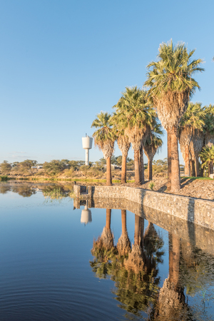 Sunset view with reflections of palm trees of the dam and reservoir at Gross Barmen, near Okahandja in the Otjozondjupa Region of Namibia Stock Photo