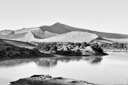 A rare sight: Sossusvlei in the Namib desert of Namibia filled with water. Big Daddy, one of the highest dunes in the world, is in the background. Monochrome