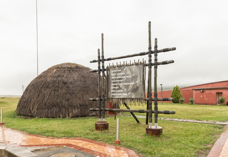 BLOEDRIVIER, SOUTH AFRICA - MARCH 22, 2018: An information board and Zulu hut at the Ncome Zulu Heritage Museum at Bloedrivier (blood river) where the Voortrekkers defeated the Zulu Impis 16-12-1838