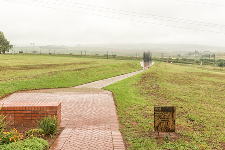 HOWICK, SOUTH AFRICA - MARCH 23, 2018: The final information plaque along the path with the statue of Nelson Mandela at his capture site in the back. At a specific viewpoint, the colums combine to form his face