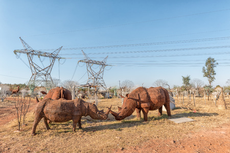 PRETORIA, SOUTH AFRICA, JULY 30, 2018: Life size rhinos, made from tin plate, for sale next to a road in Pretoria in the Gauteng Province of South Africa. Power lines are visible Redactioneel