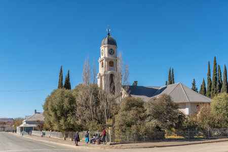 PETRUSVILLE, SOUTH AFRICA, AUGUST 6, 2018: A street scene, with the Dutch Reformed Church, in Petrusville in the Northern Cape Province. People are visible