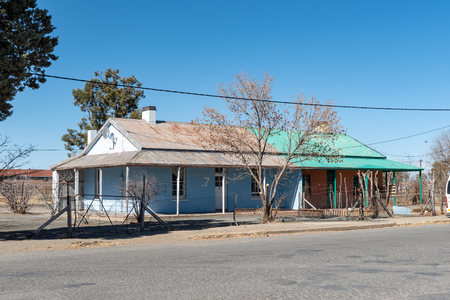 DE AAR, SOUTH AFRICA, AUGUST 6, 2018: A street scene, with an historic semi-detached house, in De Aar in the Northern Cape Province