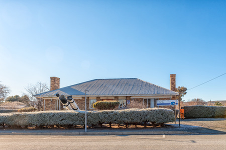 SUTHERLAND, SOUTH AFRICA, AUGUST 8, 2018: A street scene with a building, one person and telescopes in Sutherland in the Northern Cape Province. Frost is visible