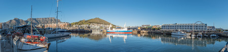 CAPE TOWN, SOUTH AFRICA, AUGUST 9, 2018:  Panorama of ships in the Alfred Basin at the Victoria and Alfred Waterfront in Cape Town in the Western Cape Province. Table Mountain and Devils Peak are visible in the back
