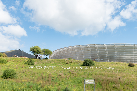 CAPE TOWN, SOUTH AFRICA, AUGUST 17, 2018: Fort Wynand with the Cape Town Stadium at Green Point in the back. A cannon and people are visible Editorial