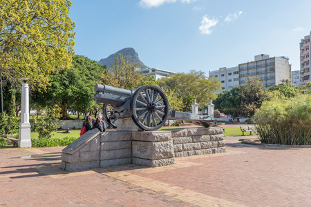 CAPE TOWN, SOUTH AFRICA, AUGUST 17, 2018: A memorial, for all artillerymen who died for their country, in the Company Gardens in Cape Town. Lions Head and tourists are visible