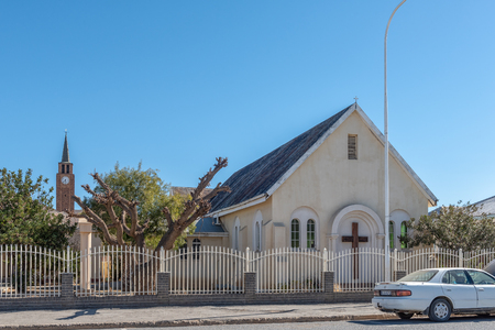 DE AAR, SOUTH AFRICA, AUGUST 6, 2018: A street scene, with the Methodist Church, in De Aar in the Northern Cape Province. The tower of the Dutch Reformed Mother Church is visible