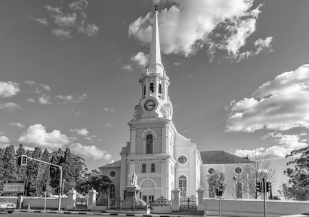 WELLINGTON, SOUTH AFRICA, AUGUST 8, 2018: A street scene, with the Dutch Reformed Mother Church, in Wellington in the Western Cape Province. A statue of reverent Andrew Murray is visible. Monochrome Editorial