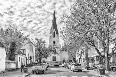 STELLENBOSCH, SOUTH AFRICA, AUGUST 15, 2018: Church Street with the historic Dutch Reformed Mother Church in Stellenbosch in the Western Cape Province. Vehicles and people are visible. Monochrome