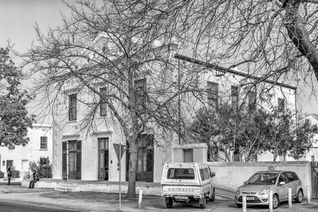 STELLENBOSCH, SOUTH AFRICA, AUGUST 15, 2018: The historic Berghuis (mountain house) in Stellenbosch in the Western Cape Province. Vehicles are visible. Monochrome
