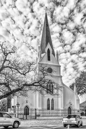 STELLENBOSCH, SOUTH AFRICA, AUGUST 15, 2018: The historic Dutch Reformed Mother Church in Stellenbosch in the Western Cape Province. Vehicles are visible. Monochrome Editorial