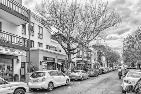 STELLENBOSCH, SOUTH AFRICA, AUGUST 16, 2018: Church Street with the historic Dutch Reformed Mother Church visible. Vehicles, businesses and people are visible. Monochrome Imagens - 121053773