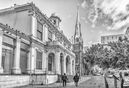 CAPE TOWN, SOUTH AFRICA, AUGUST 17, 2018: A view of Greenmarket Square in Cape Town in the Western Cape Province. The Iziko Old Town House Museum and the Central Methodist Mission Church are visible. Monochrome Imagens - 121053777