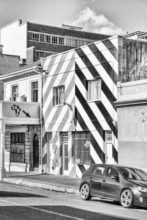 CAPE TOWN, SOUTH AFRICA, AUGUST 17, 2018: A surf shop in the Bo-Kaap in Cape Town in the Western Cape Province. A vehicle is visible. Monochrome Editorial