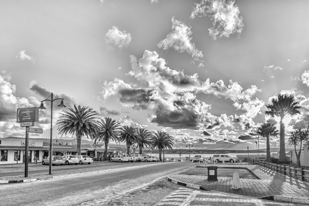 LANGEBAAN, SOUTH AFRICA, AUGUST 20, 2018: A late afternoon street scene, with businesses and vehicles, in Langebaan in the Western Cape Province. Monochrome