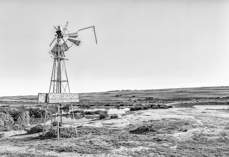 VREDENBURG, SOUTH AFRICA, AUGUST 21, 2018: A funny sign on a broken windmill near Vredenburg in the Western Cape Province. Monochrome