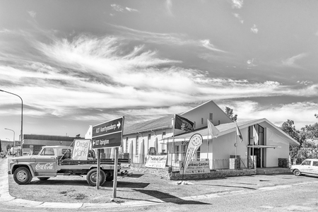 CALVINIA, SOUTH AFRICA, AUGUST 30, 2018: Hall of the Dutch Reformed Mother Church in Calvinia in the Northern Cape Province. A vintage pick-up truck is visible. Monochrome Imagens - 121148857