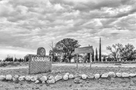 VOSBURG, SOUTH AFRICA, SEPTEMBER 1, 2018: A name board and directional sign at the entrance to Vosburg in the Northern Cape Province. Monochrome