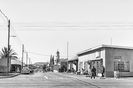 PETRUSVILLE, SOUTH AFRICA, AUGUST 6, 2018: A street scene with businesses, people  and vehicles, in Petrusville in the Northern Cape Province. The Dutch Reformed Church is visible. Monochrome