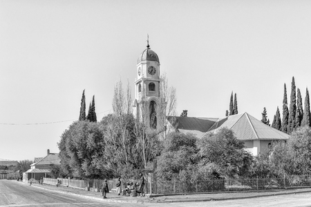 PETRUSVILLE, SOUTH AFRICA, AUGUST 6, 2018: A street scene, with the Dutch Reformed Church, in Petrusville in the Northern Cape Province. People are visible. Monochrome