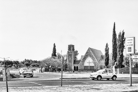 WELKOM, SOUTH AFRICA, AUGUST 2, 2018: A street scene, with the St Matthias Anglian Church, in Welkom in the Free State Province Province. Vehicles are visible. Monochrome Imagens - 121148894