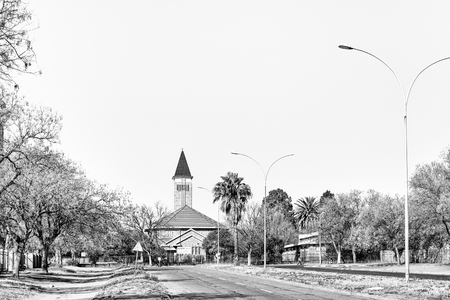 VIRGINIA, SOUTH AFRICA, AUGUST 2, 2018: The Dutch Reformed Church in Virginia in the Free State Province Province. Trees and lamp posts are visible. Monochrome