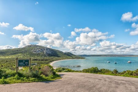 WEST COAST NATIONAL PARK, SOUTH AFRICA, AUGUST 20, 2018: Road to Kraalbaai at the Langebaan Lagoon on the Atlantic Ocean coast of the Western Cape Province. A jetty and houseboats are visible