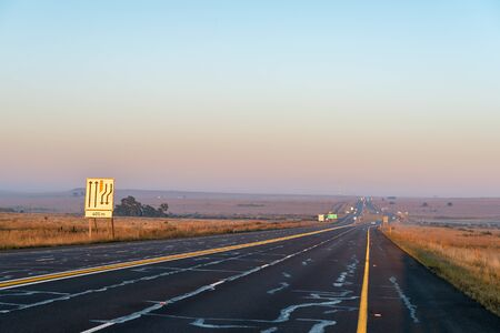 The sun is rising over road N1 at the Verkeerdevlei junction north of Bloemfontein, South Africa