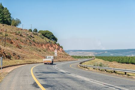 CAROLINA, SOUTH AFRICA - MAY 2, 2019: Road landscape next to road R38 between Carolina and Badplaas in the Mpumalanga Province of South Africa. A truck and pine tree plantations are visible