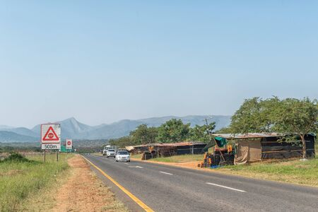 BARBERTON, SOUTH AFRICA - MAY 2, 2019: Vendor stalls on road R38 near Barberton in the Mpumalanga Province. Road signs and vehicles are visible