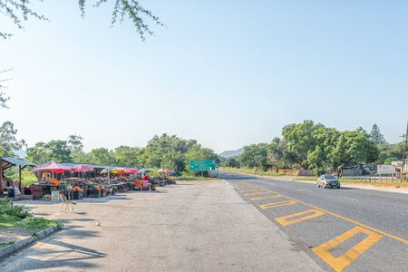NELSPRUIT, SOUTH AFRICA - MAY 3, 2019: Vendor stalls next to road N4 between Nelspruit and Malalane in the Mpumalanga Province. A vehicle and directional sign are visible