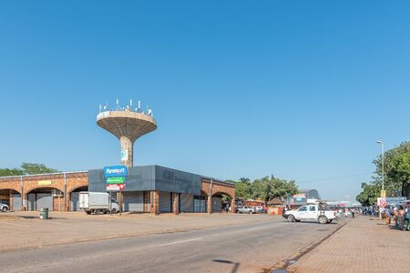 MALELANE, SOUTH AFRICA - MAY 3, 2019: A street scene, with businesses, street vendors and people, in Malelane in the Mpumalanga Province. A water tower is visible