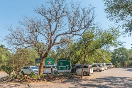 KRUGER NATIONAL PARK, SOUTH AFRICA - MAY 3, 2019: Parking area in the Berg en Dal Rest Camp in the Kruger National Park. Vehicles and information boards are visible